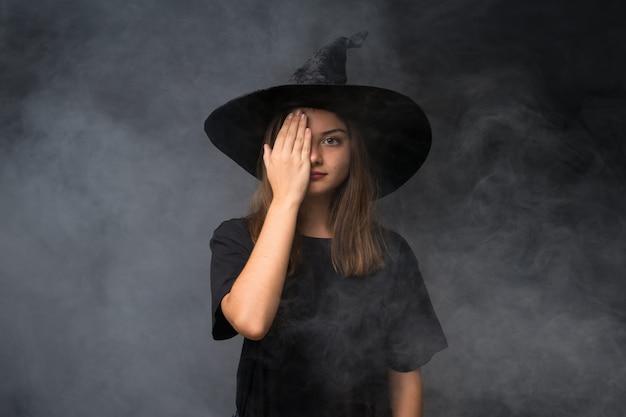 Meisje met heksenkostuum voor halloween-partijen over geïsoleerde donkere muur die een oog met de hand behandelen