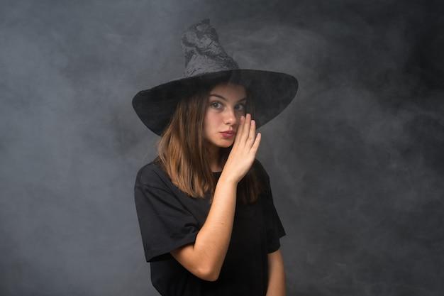 Meisje met heksenkostuum voor halloween-partijen over geïsoleerde donkere muur die iets fluisteren