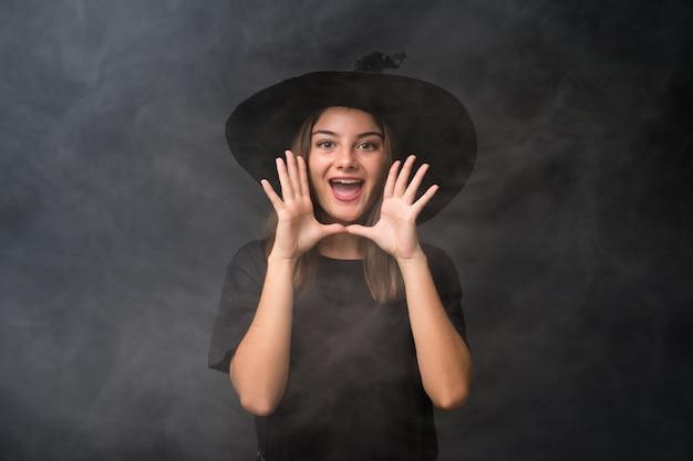 Meisje met heksenkostuum voor halloween-partijen over geïsoleerde donkere muur die met wijd open mond schreeuwen