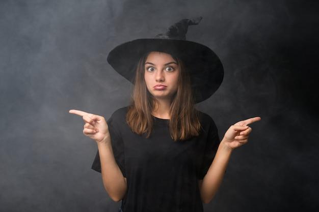 Meisje met heksenkostuum voor halloween-partijen over geïsoleerde donkere muur die naar de zijtakken wijzen die twijfels hebben