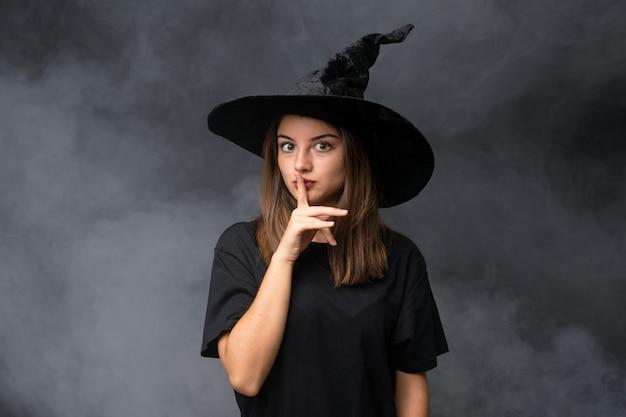 Meisje met heksenkostuum voor halloween-partijen over geïsoleerde donkere muur die stiltegebaar doen