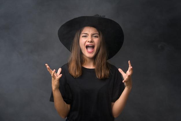 Meisje met heksenkostuum voor halloween-partijen over geïsoleerde donkere muur ongelukkig en gefrustreerd met iets