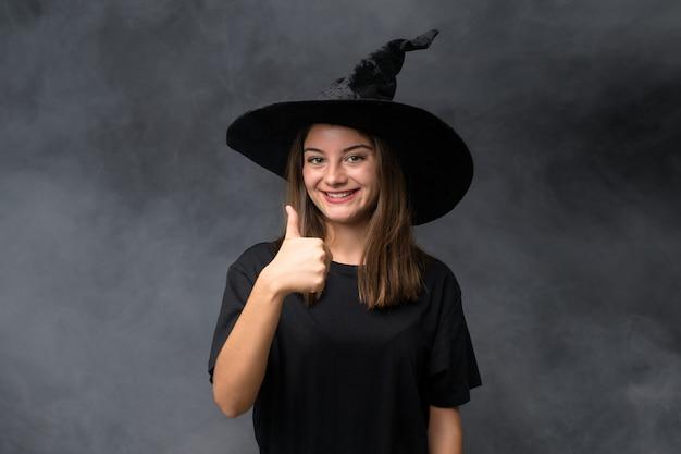 Meisje met heksenkostuum voor halloween-partijen over het geïsoleerde donkere muur geven duimen op gebaar
