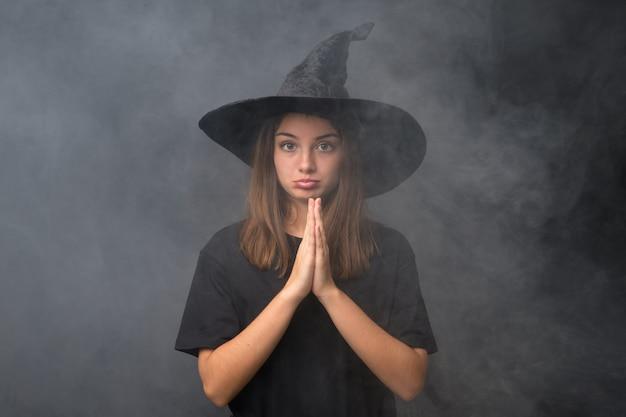 Meisje met heksenkostuum voor halloween-partijen over het geïsoleerde donkere muur pleiten