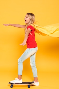 Meisje met heldenkostuum op skateboard