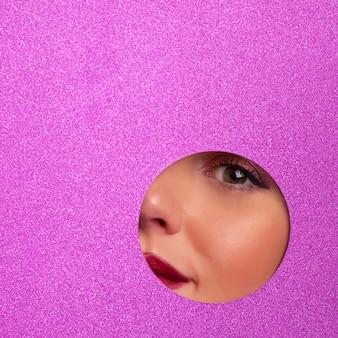 Meisje met heldere ogen make-up kijkt door gat in violet papier