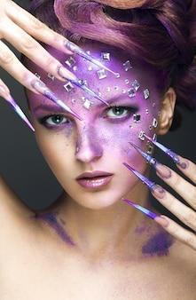 Meisje met heldere paarse creatieve make-up met kristallen en lange nagels. mooi gezicht. foto genomen in de studio op een grijze achtergrond.