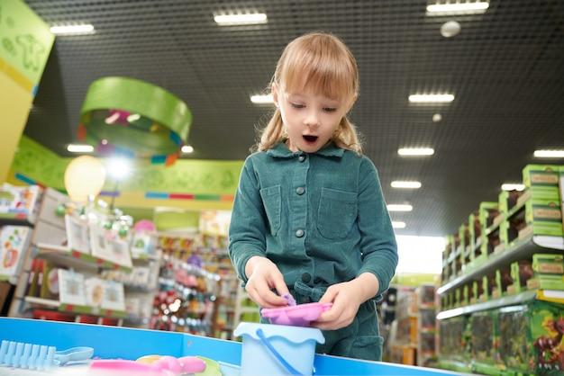 Meisje met het open mond spelen met plasticine in stuk speelgoed opslag
