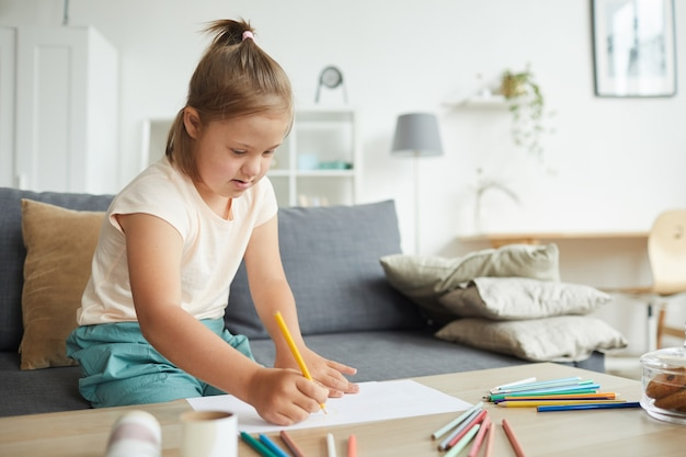 Meisje met het syndroom van down aan de tafel zitten en afbeelding tekenen met kleurrijke potloden in de huiskamer