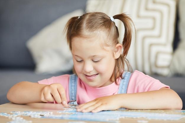 Meisje met het syndroom van down aan de tafel zitten en leren puzzels te verzamelen
