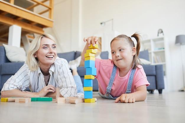 Meisje met het syndroom van down bouwt samen met haar moeder op de vloer thuis een toren van gekleurde blokken