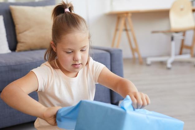 Meisje met het syndroom van down die het inpakpapier op de doos scheurt en haar cadeau thuis opent