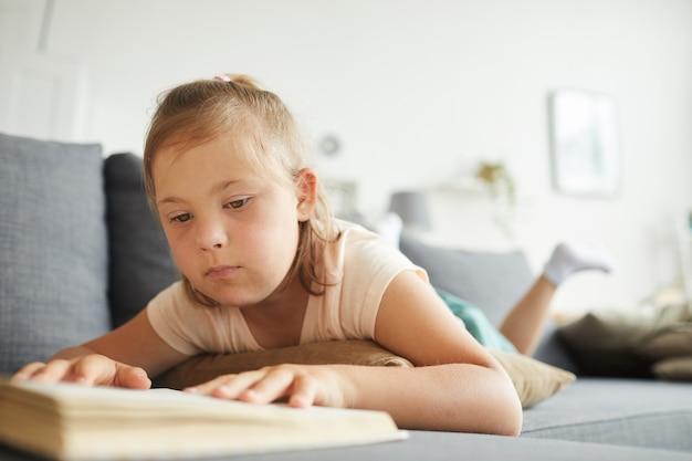 Meisje met het syndroom van down die op bank liggen en een boek in de woonkamer lezen