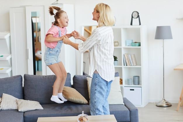 Meisje met het syndroom van down die op de bank springt die zij met haar moeder speelt terwijl zij thuis zijn