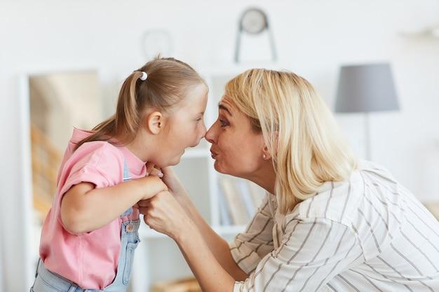 Meisje met het syndroom van down en haar moeder kijken elkaar aangezicht tot aangezicht ze spelen thuis