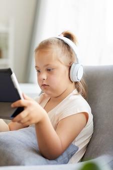 Meisje met het syndroom van down hoofdtelefoon dragen en kijken naar tekenfilms op digitale tablet zittend op de bank in de kamer