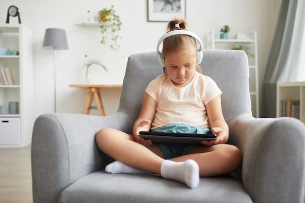 Meisje met het syndroom van down hoofdtelefoon dragen en met behulp van digitale tablet voor online onderwijs zittend op een stoel in de kamer