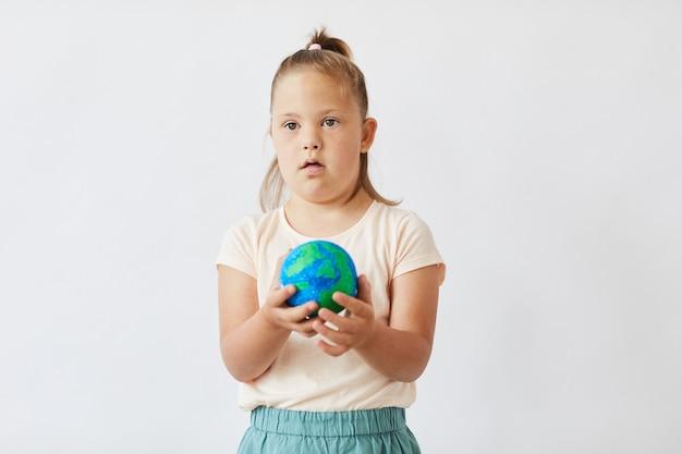 Meisje met het syndroom van down houdt model van de planeet aarde in haar handen terwijl ze tegen de witte achtergrond staat