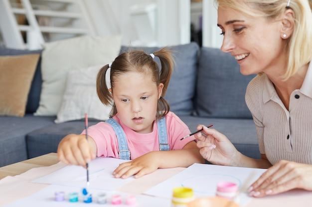 Meisje met het syndroom van down leren schilderen aan tafel terwijl haar moeder haar in de kamer helpt