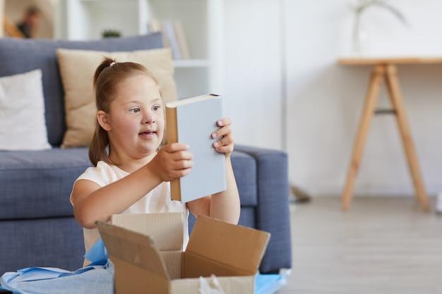 Meisje met het syndroom van down neemt het boek uit de doos terwijl ze in de kamer zit