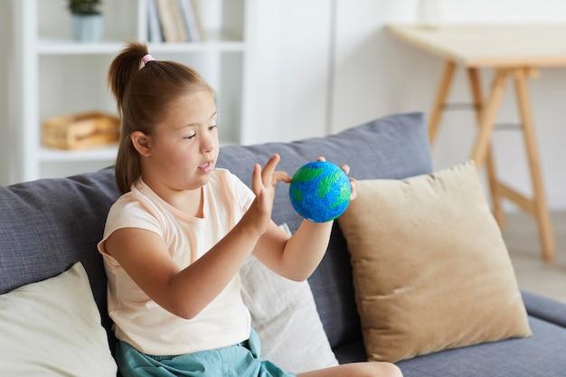 Meisje met het syndroom van down, onderzoekt het model van de planeet aarde zittend op de bank thuis