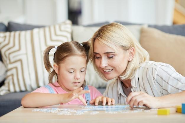 Meisje met het syndroom van down puzzels aan het verzamelen aan tafel met de hulp van haar moeder, ze zijn in de kamer thuis