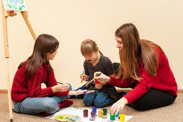 Meisje met het syndroom van down schilderen met kleuren