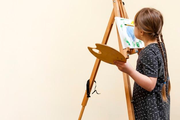 Meisje met het syndroom van down schilderen met kopie ruimte