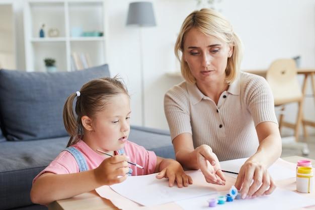 Meisje met het syndroom van down schilderen met verf samen met haar moeder aan de tafel thuis