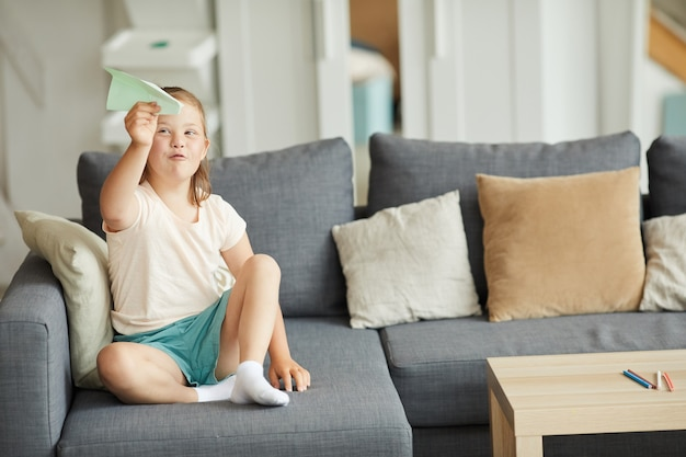 Meisje met het syndroom van down, zittend op de bank en spelen met papieren vliegtuigje in de woonkamer