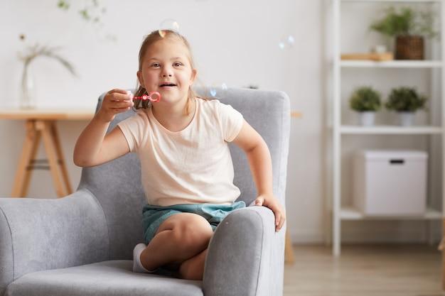 Meisje met het syndroom van down, zittend op een stoel en bellen blazen thuis