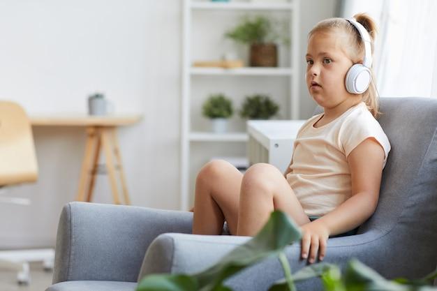 Meisje met het syndroom van down zittend op een stoel in draadloze hoofdtelefoons en luisteren naar muziek in de kamer
