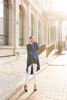 Meisje met hijab, luisteren naar muziek via een koptelefoon buiten