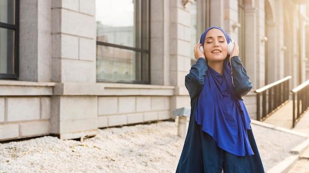 Meisje met hijab luisteren naar muziek via koptelefoon met kopie ruimte