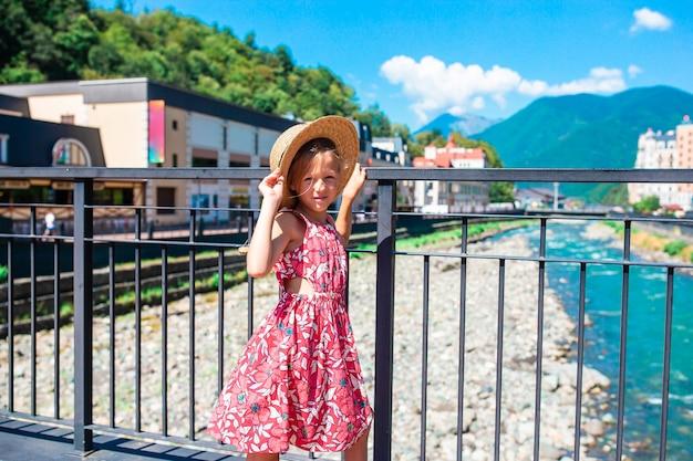 Meisje met hoed aan de kade van een bergrivier in een europese stad.