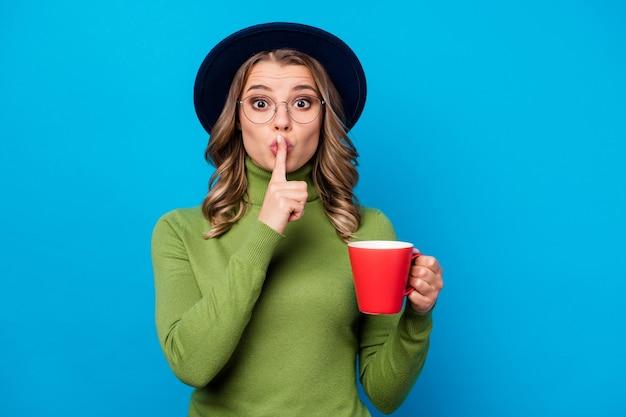 Meisje met hoed en glazen beker geïsoleerd op blauw te houden