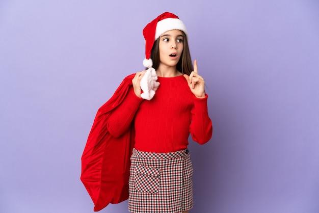 Meisje met hoed en kerstmiszak die op purpere muur wordt geïsoleerdm die een idee denken dat de vinger omhoog wijst
