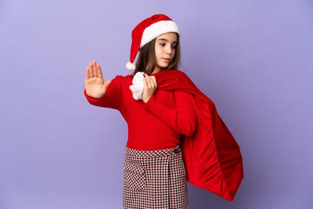 Meisje met hoed en kerstmiszak geïsoleerd