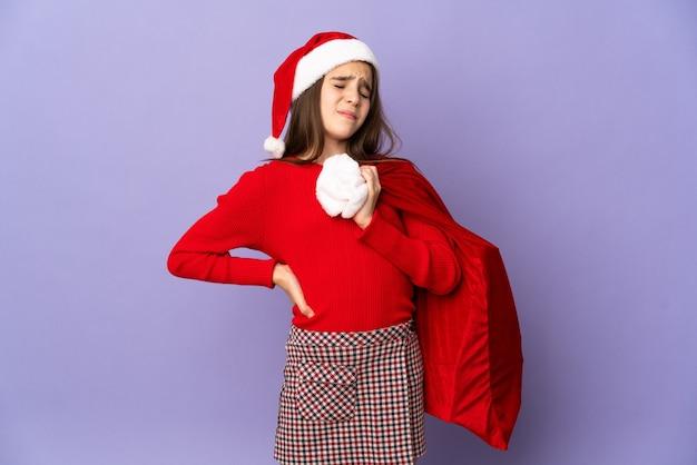 Meisje met hoed en kerstzak geïsoleerd op paarse achtergrond die lijdt aan rugpijn omdat ze zich heeft ingespannen