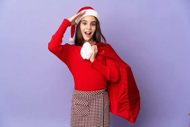 Meisje met hoed en kerstzak geïsoleerd op paarse achtergrond met verrassing expressie