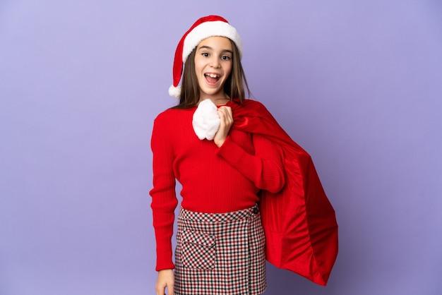Meisje met hoed en kerstzak geïsoleerd op paarse achtergrond met verrassingsgelaatsuitdrukking
