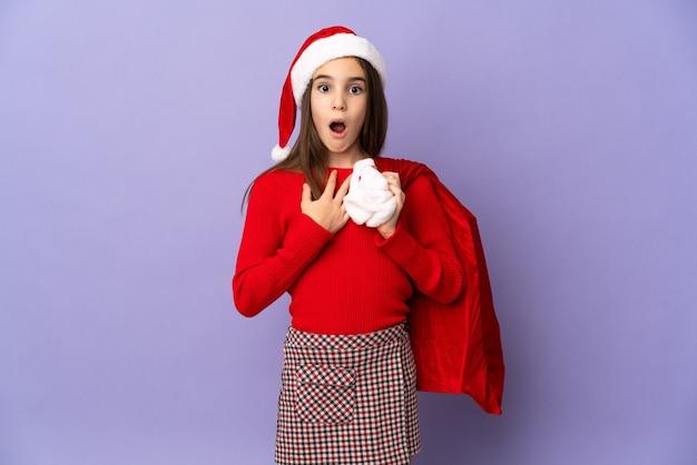 Meisje met hoed en kerstzak geïsoleerd op paarse achtergrond verrast en geschokt terwijl je naar rechts kijkt