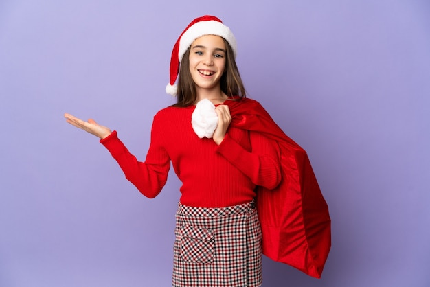 Meisje met hoed en kerstzak geïsoleerd op paarse muur met geschokt gelaatsuitdrukking