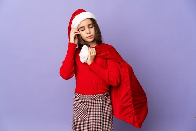 Meisje met hoed en kerstzak geïsoleerd op paarse muur met hoofdpijn