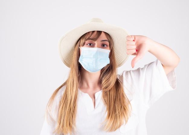 Meisje met hoed en masker, verdrietig omdat ze niet kan reizen
