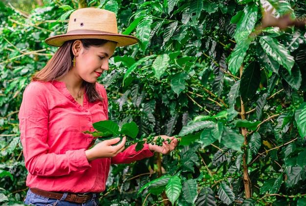 Meisje met hoed en roze overhemd in koffieplantage
