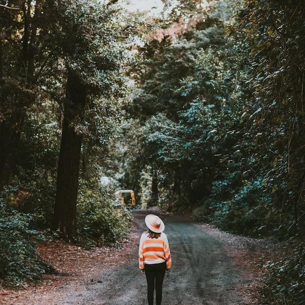 Meisje met hoed wandelen in het bos