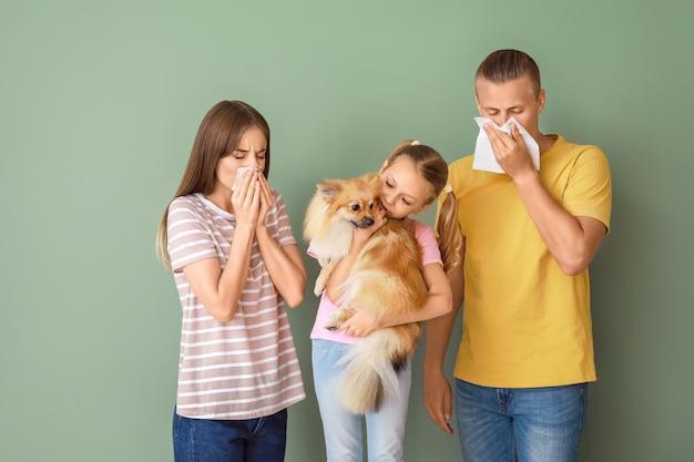 Meisje met hond en ouders die aan huisdierenallergie op kleur lijden