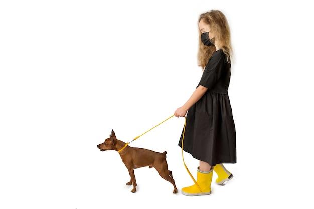 Meisje met hond, zwarte en gele kleren. witte achtergrond. studio-opnamen. baby huisdieren concept, gelukkige jeugd. hoge kwaliteit foto