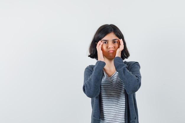 Meisje met hoofdpijn in t-shirt, jasje en moe op zoek.